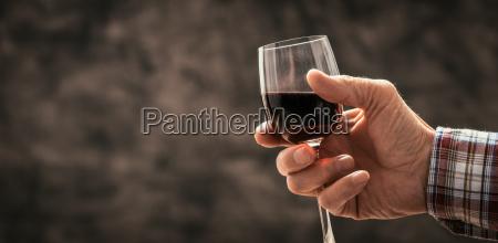 mann der ein glas rotwein schmeckt