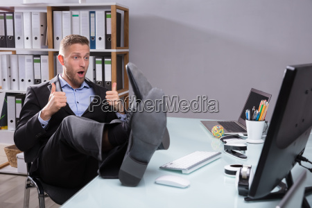 young businessman gesturing thumbs up