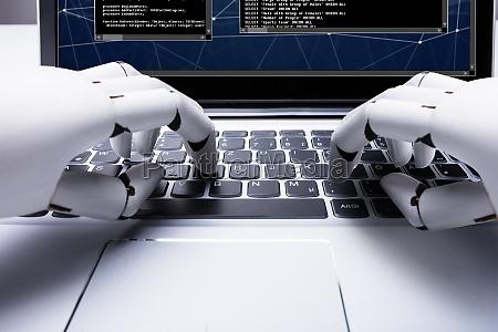roboter der auf laptop tastatur schreibt