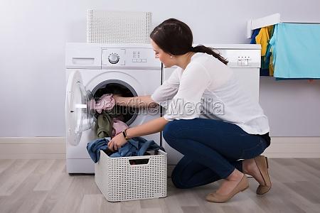 frau laden kleidung in waschmaschine