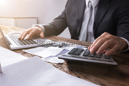 businesspersons hand using calculator