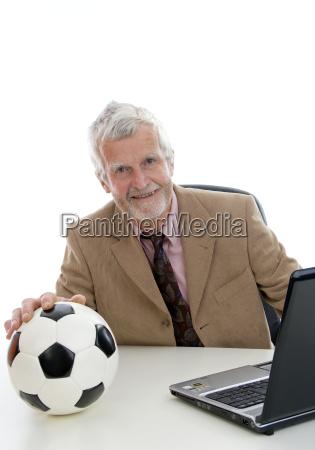 aelterer geschaftsmann mit fussball und laptop