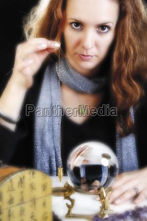 wahrsagerin mit pendel und kristallkugel
