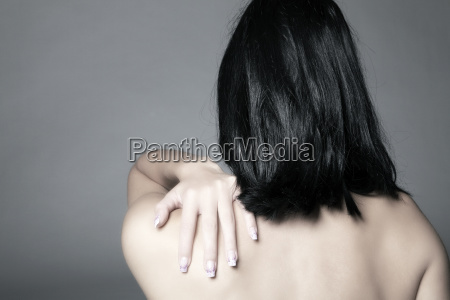 young woman massages her back