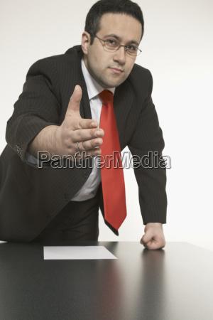 geschaftsmann am schreibtisch hebt die hand