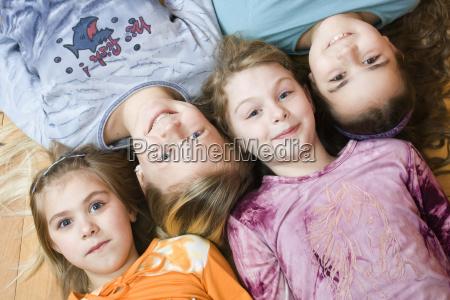 group of 4 little girls lying