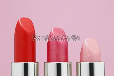 lippenstifte in einer reihe vor rosa