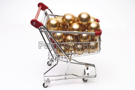 einkaufswagen mit christbaumkugeln symbolbild weihnachtseinkaufe