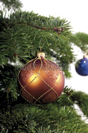 kupferfarbene weihnachtskugel an tannenbaumzweig