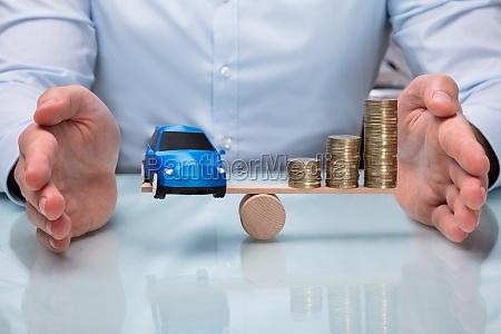 geschaeftsmann der balance zwischen auto und
