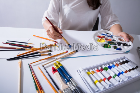 female artist painting on canvas paper
