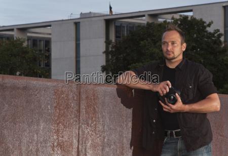 fotograf steht im berliner regierungsviertel und