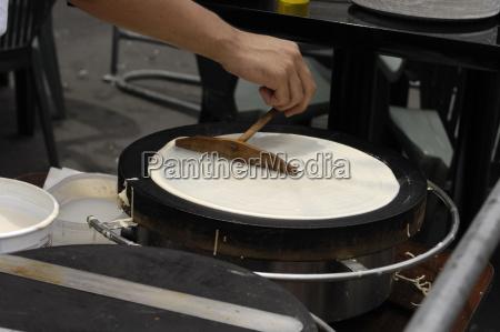 person brat einen pfannkuchen crepe