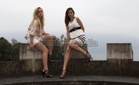 zwei junge frauen posieren auf schlossmauer