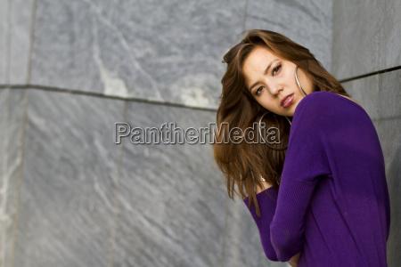 junge frau in lila kleid posiert