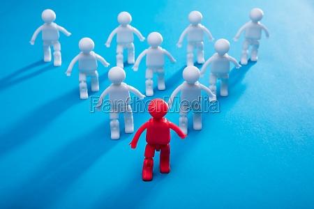 red human figure leading team toward
