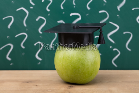 green apple with graduation hat on