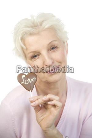 eine altere frau halt ein schokoladenherz