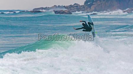 surfer springt auf der grossen welle