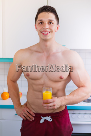 bodybuilder young man drinks drinking orange