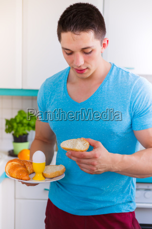 young man eat breakfast in the