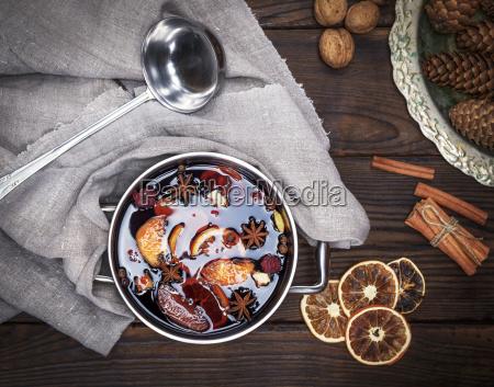 gluehwein mit gewuerzen und fruchtstuecken in