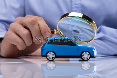 person holding magnifying glass over car