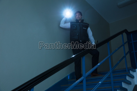 male security guard standing on staircase