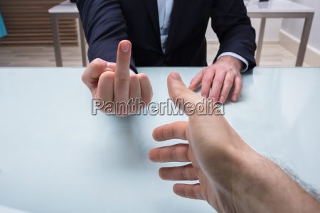 businessman showing middle finger to his