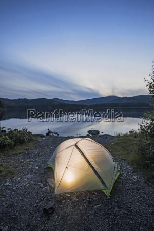 camping tent on lakeshore at evening