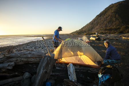 people setting up tent at beach