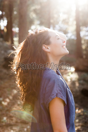 smiling carefree woman in sunny woods
