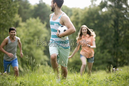 couples running through summer field with