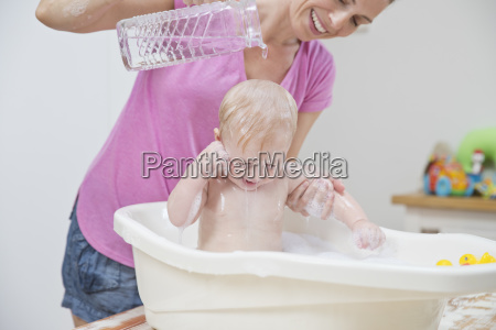 mother washing baby sons hair in