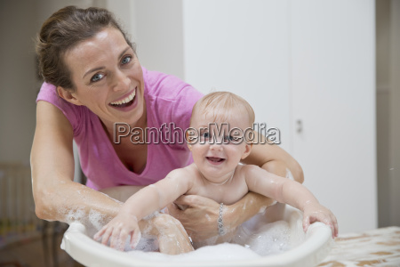 portrait of mother washing baby son