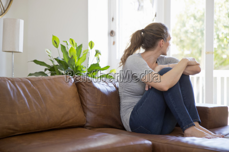 depressed woman sitting on sofa and