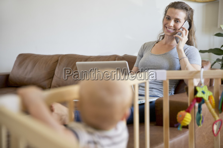 smiling mother on phone with laptop