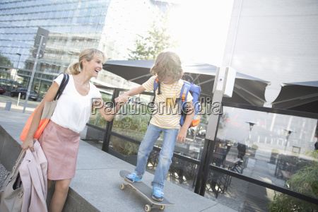 businesswoman mother playing with son on