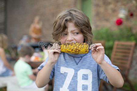 boy eating sweetcorn outdoors at home