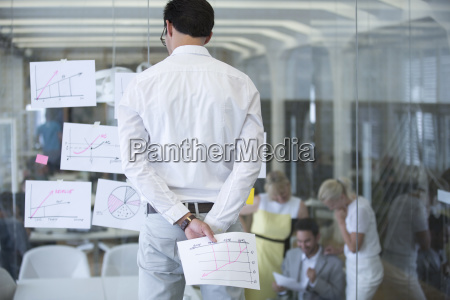 businessman studying documents stuck to glass