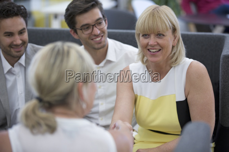businesspeople meeting in lobby of modern