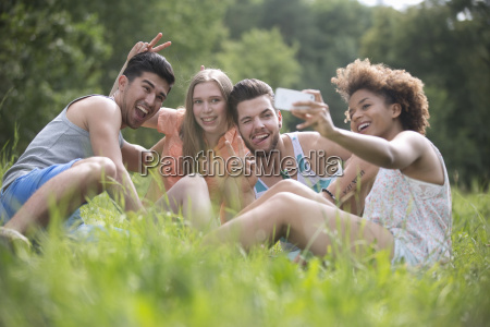 young couples pose for selfie sitting