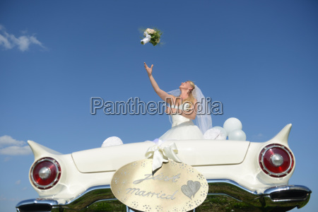 bride throwing bouquet from open top