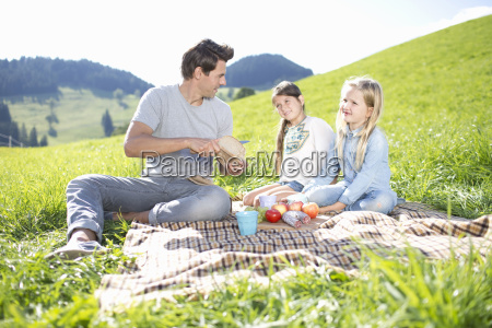 fathers with daughters enjoying countryside picnic