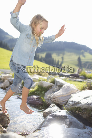 young girl jumping across countryside stream
