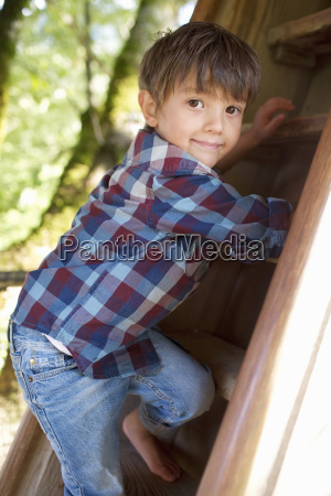 young boy climbing ladder in adventure