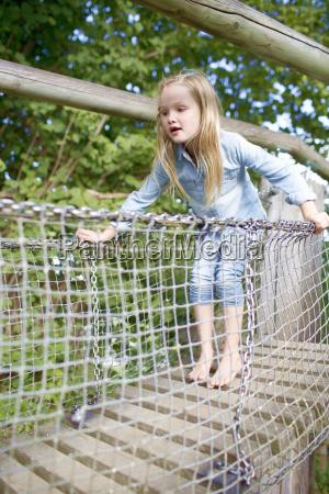 young girl crossing bridge in adventure
