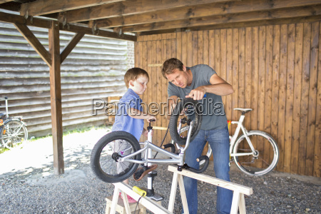 father and son mending bicycle in