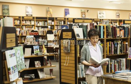 asian american female browsing through books