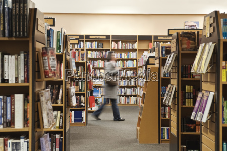 caucasian female browsing through books in